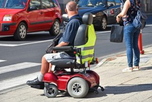 Man on a electric wheelchair crossing the street