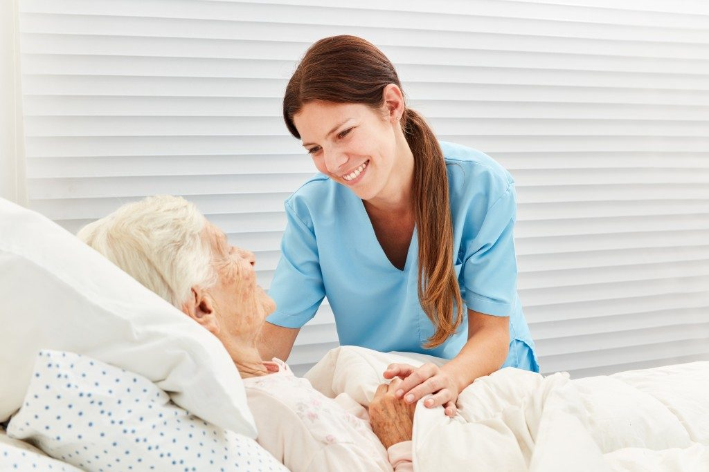 Elderly woman lying on bed with her nurse