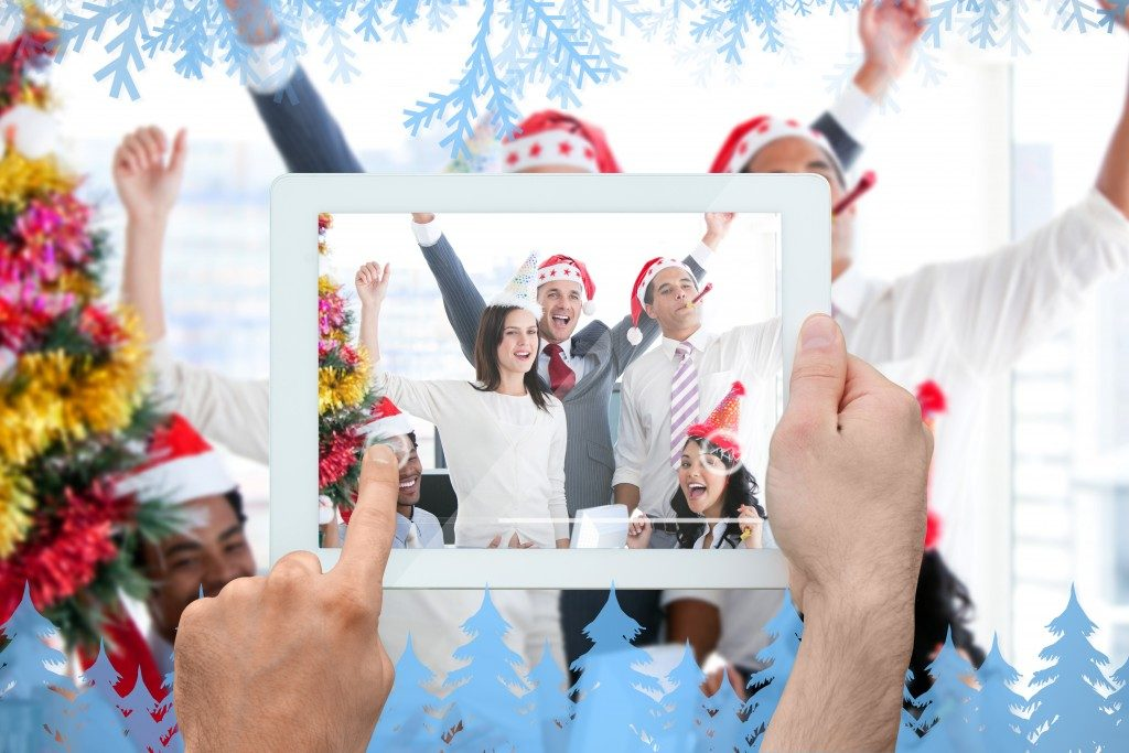 Hand holding tablet taking picture of people celebrating christmas