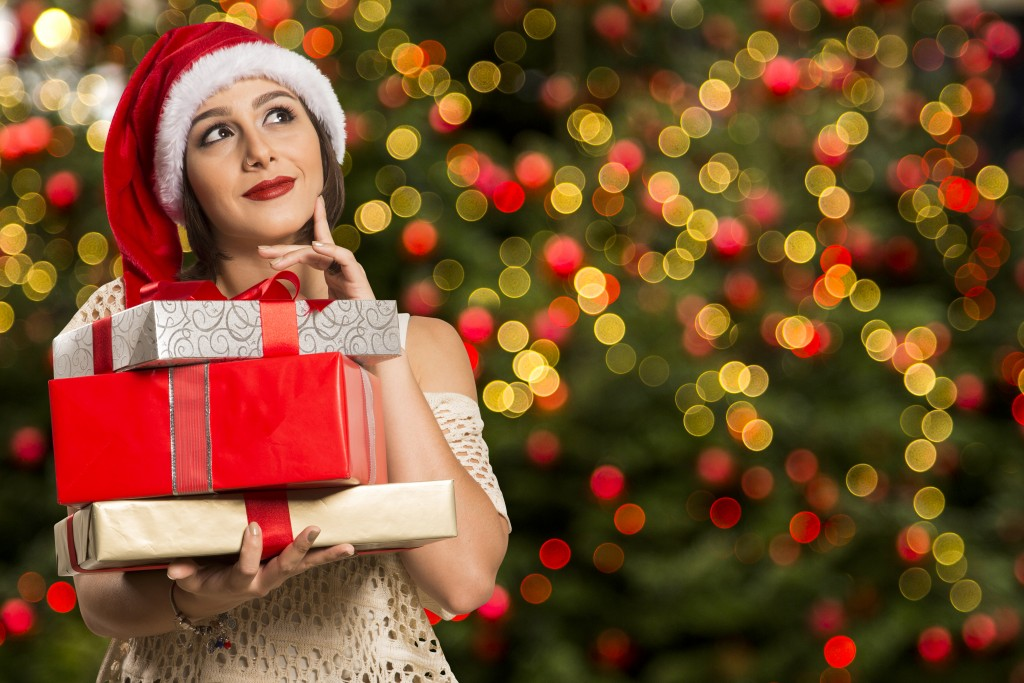 Woman with santa claus hat holding gifts