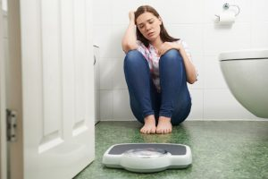 Young girl sitting on the floor next to weighing scale