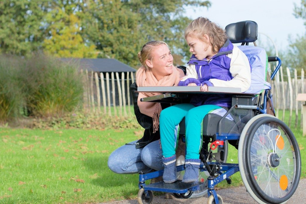 Disabled child in wheelchair being accompanied outdoors