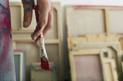 Close up of an artist holding paint brush