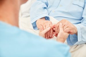 nurse holding elderly's hands