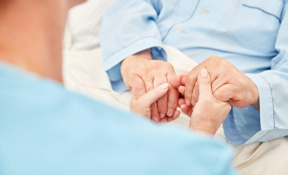 nurse holding elderly's hands