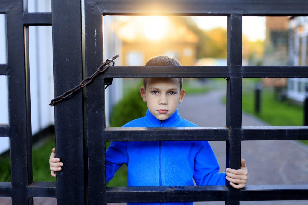 child isolated behind the gate