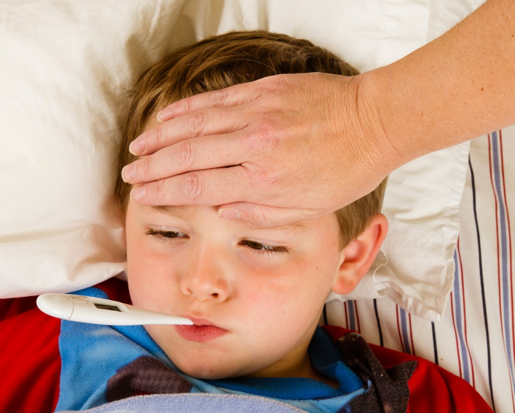 Child with flu resting in bed