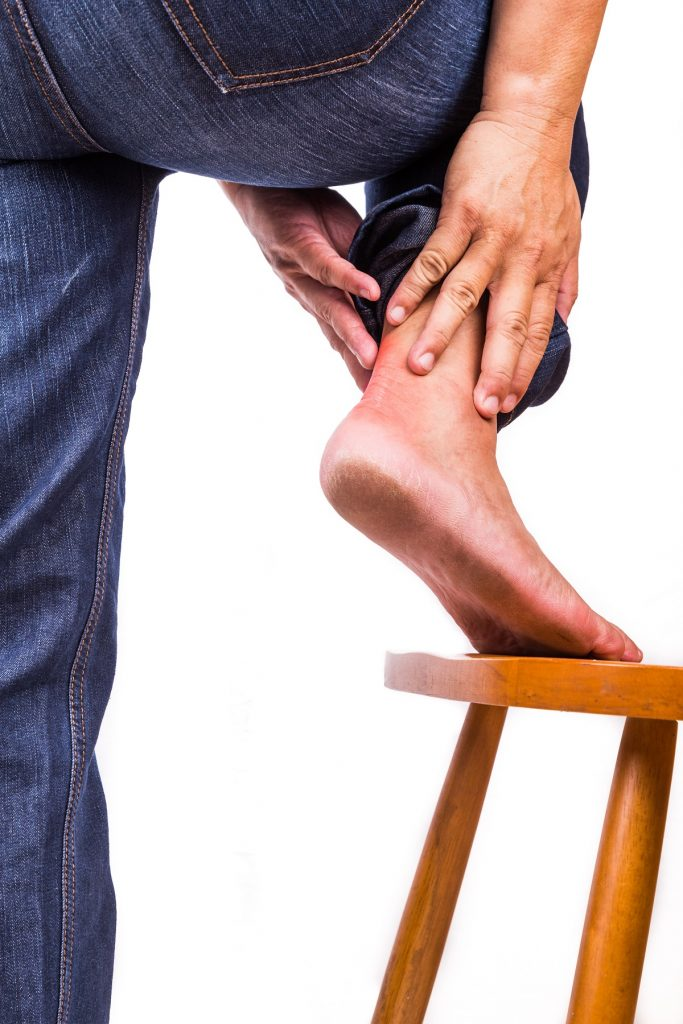 man experiencing pain near his heel