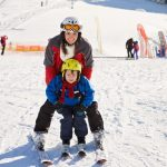 Mother and child snowboarding