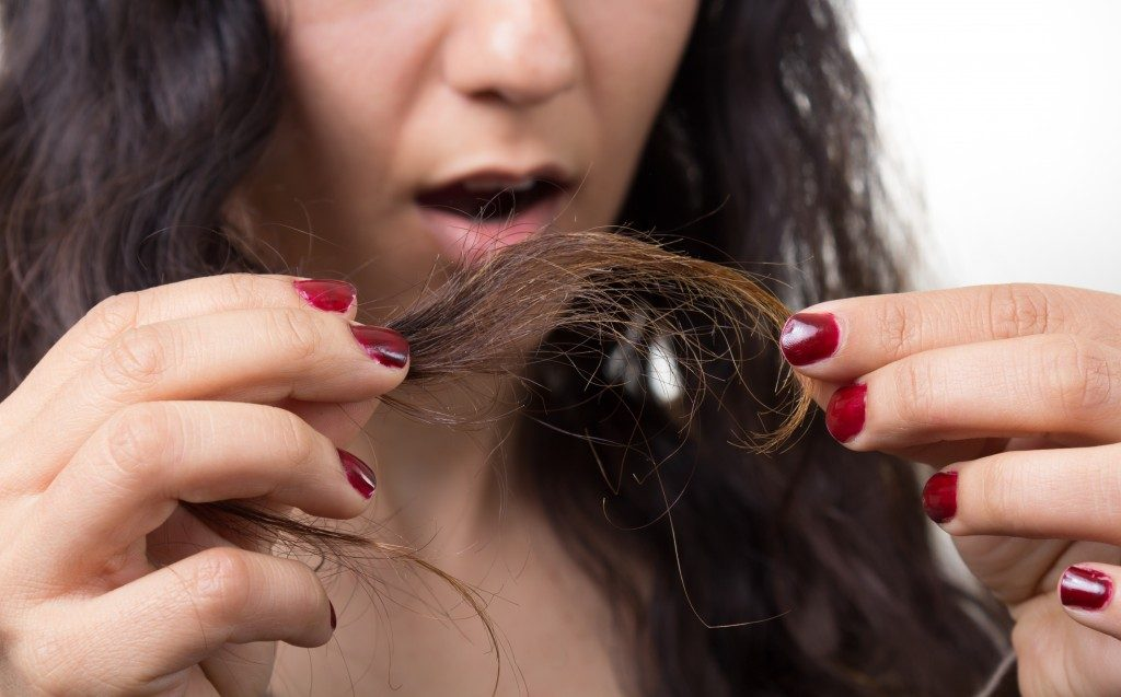 Woman looking at damaged splitting ends of hair
