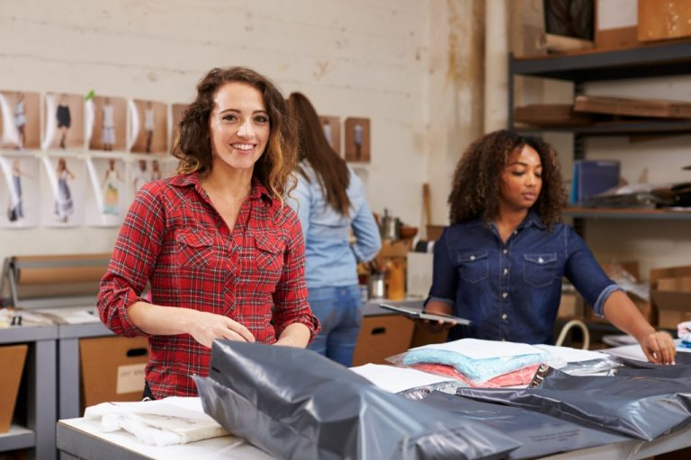 women packing clothes for delivery in their warehouse