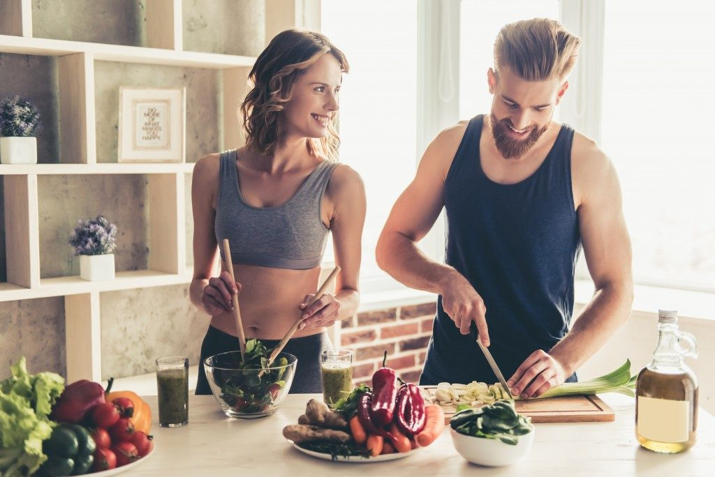 couple in workout clothes preparing high in protein snacks
