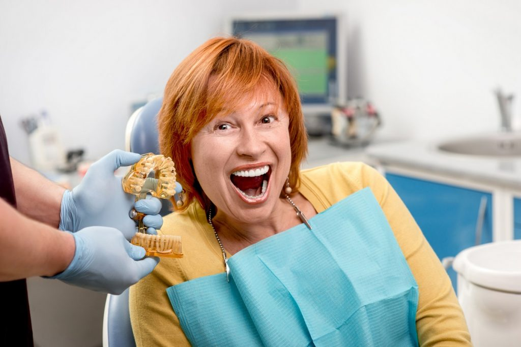 Woman smiling with her new dentures