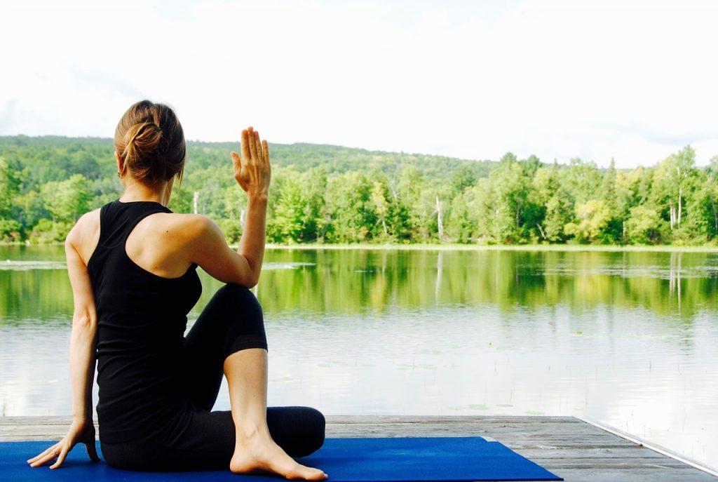 woman stretching near a lake