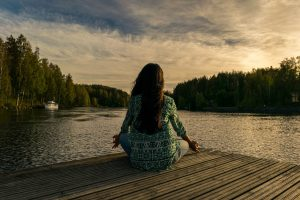 woman meditating near a lake