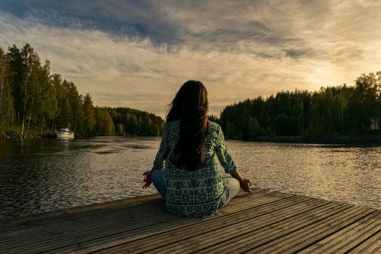 woman meditating near a lake