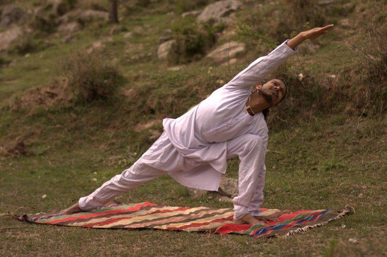 man doing yoga outdoors