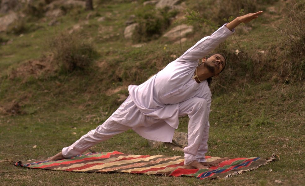 man doing yoga outdoors