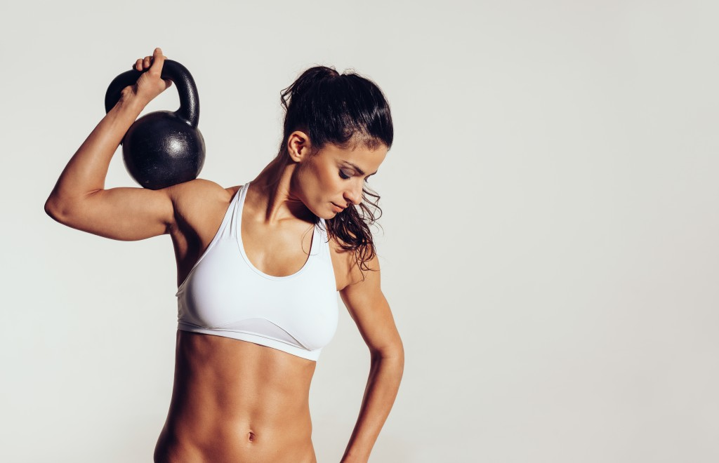 Woman in sportswear doing crossfit workout with kettle bell on grey background