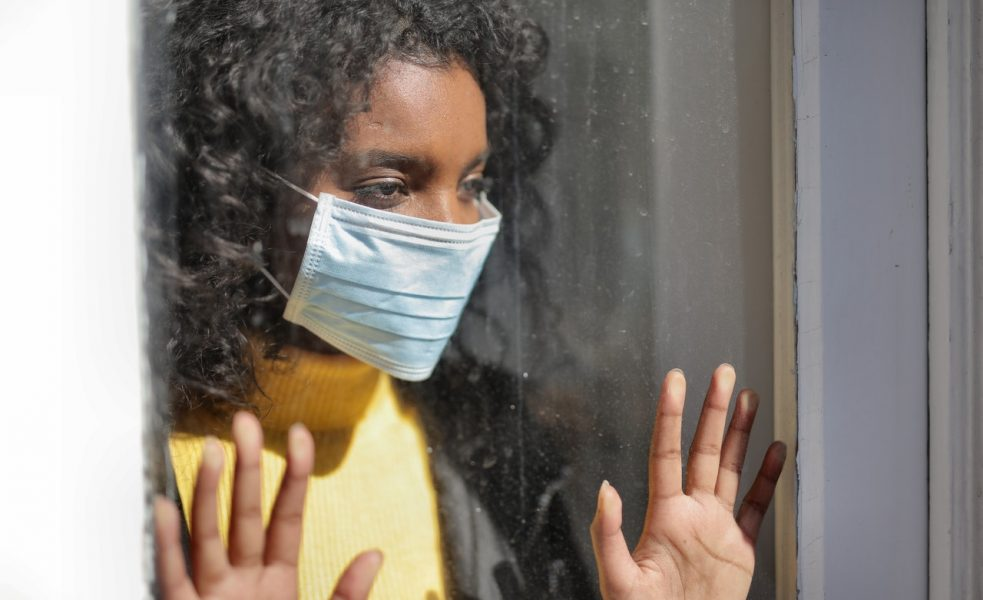 woman wearing mask looking out the window