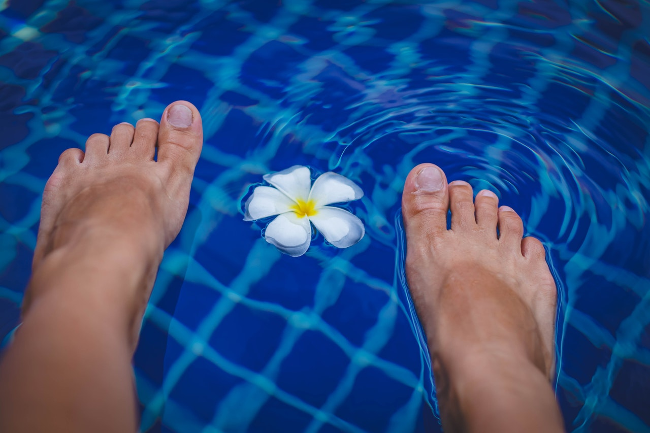 Person's Feet on Swimming Pool